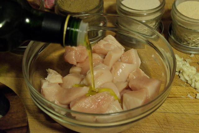 Olive oil being poured over the diced chicken in a bowl.
