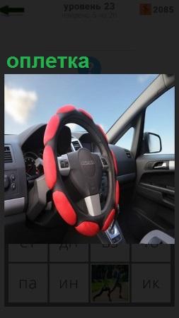 В салоне автомобиля на руле сделана цветная оплетка