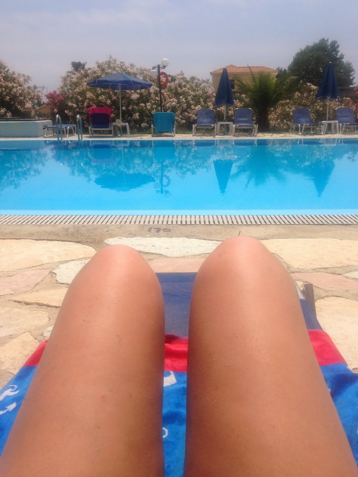 a picture of a girl's very tanned legs as she lays on a towel by the pool in kefalonia, greece