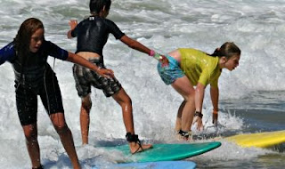 Three campers surfing side-by-side together at Aloha Beach Camp.
