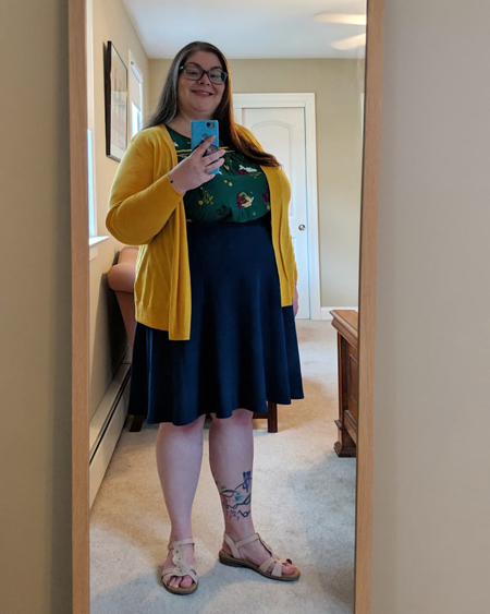image of me in a full-length mirror, with my hair down, wearing grey-framed glasses, a mustard yellow cardigan, a green top with a Wizard of Oz pattern on it, a blue skirt, and beige sandals