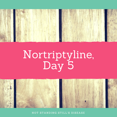 """photo of wooden planks with mint green thin bars at top and bottom - in the bottom bar white text """"Not Standing Still's Disease"""" - at middle a pinkish thicker bar with white text 'Nortriptyline, Day 5"""""""