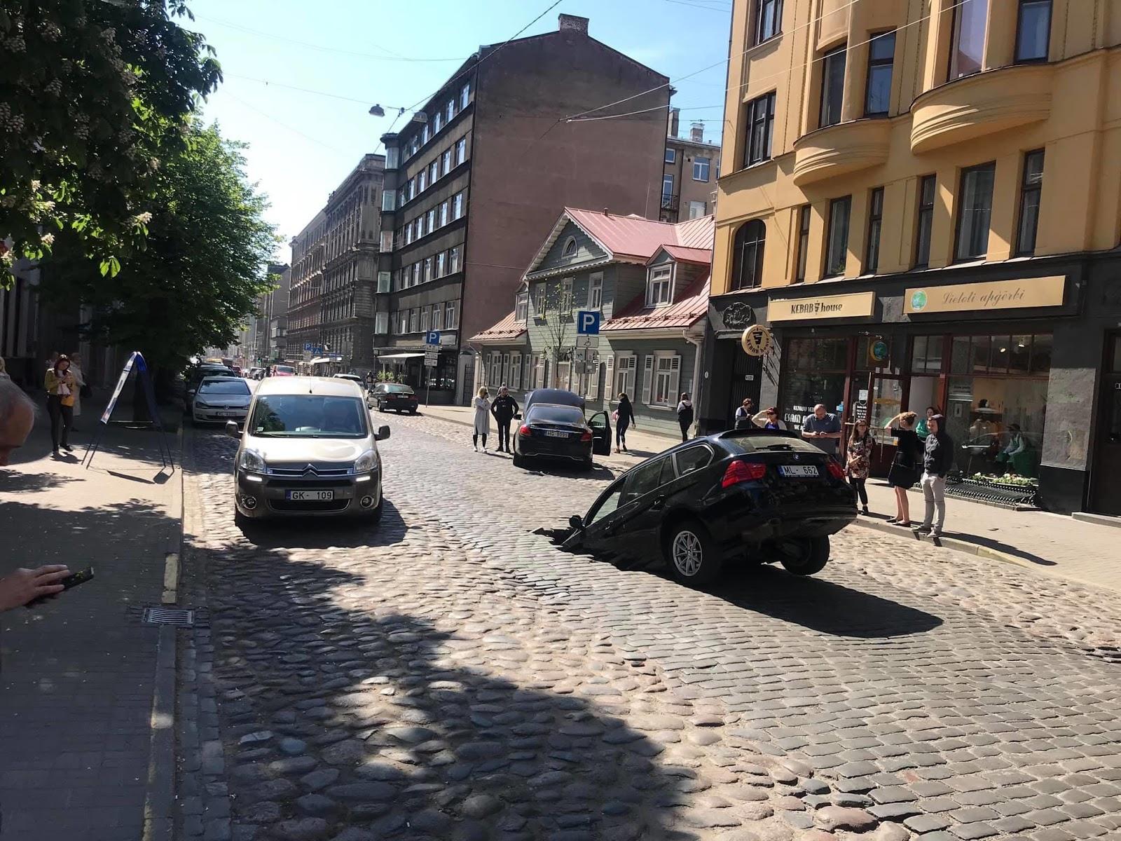 Bruģēta iela ar bedri tās vidū un auto, kas tajā iebrauca
