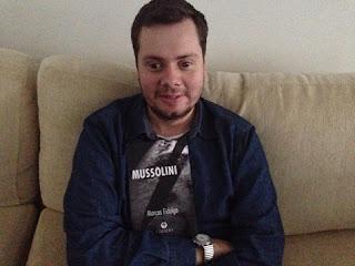 Foto de Marcos Fidalgo sentado de frente com os  braços cruzados em um sofá de tecido bege. Marcos tem a pele bem clara, rosto oval, cabelos castanhos, sobrancelhas retas, olhos amendoados, nariz levemente arrebitado, lábios médios e barba por fazer. Marcos usa camisa jeans escuro sobre camiseta branca, relógio com pulseira cromada no pulso direito, apoiado em frente ao peito de Marcos, um exemplar do recente livro dele intitulado: Mussolini, estampado em letras brancas maiúsculas brancas  sobrepostas a um fundo preto, branco e cinza com a foto do Globo terrestre ampliado e a sombra de uma  enorme faca  na diagonal com a extremidade em ponta direcionada no canto inferior esquerdo. Abaixo e centralizado em letras brancas, o nome do autor: Marcos Fidalgo, e no rodapé: o logo da editora com o nome: CHIADO.  Obs: Quem quiser comprar é só mandar uma mensagem inbox no Face: Marcos Fidalgo ou pelo  Twitter: @marcosfidalgo1