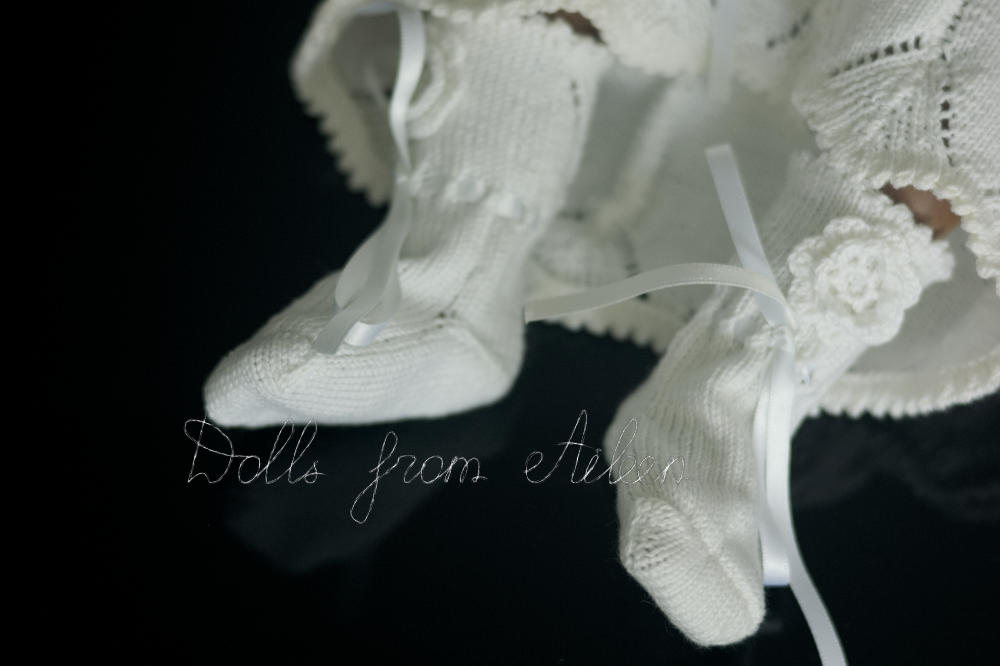 white baby booties decorated with flowers and ribbons