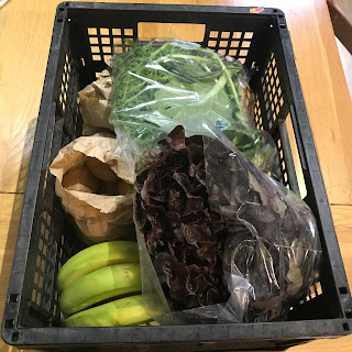 A veg box full of paper and plastic bags containing fruit and vegetables. You can just see some salad leaves, bananas and mushrooms.