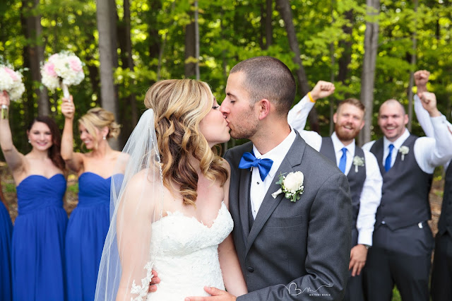 bride and groom kissing in front of bridal party at Noah's Event Venue in Auburn Hills Michigan