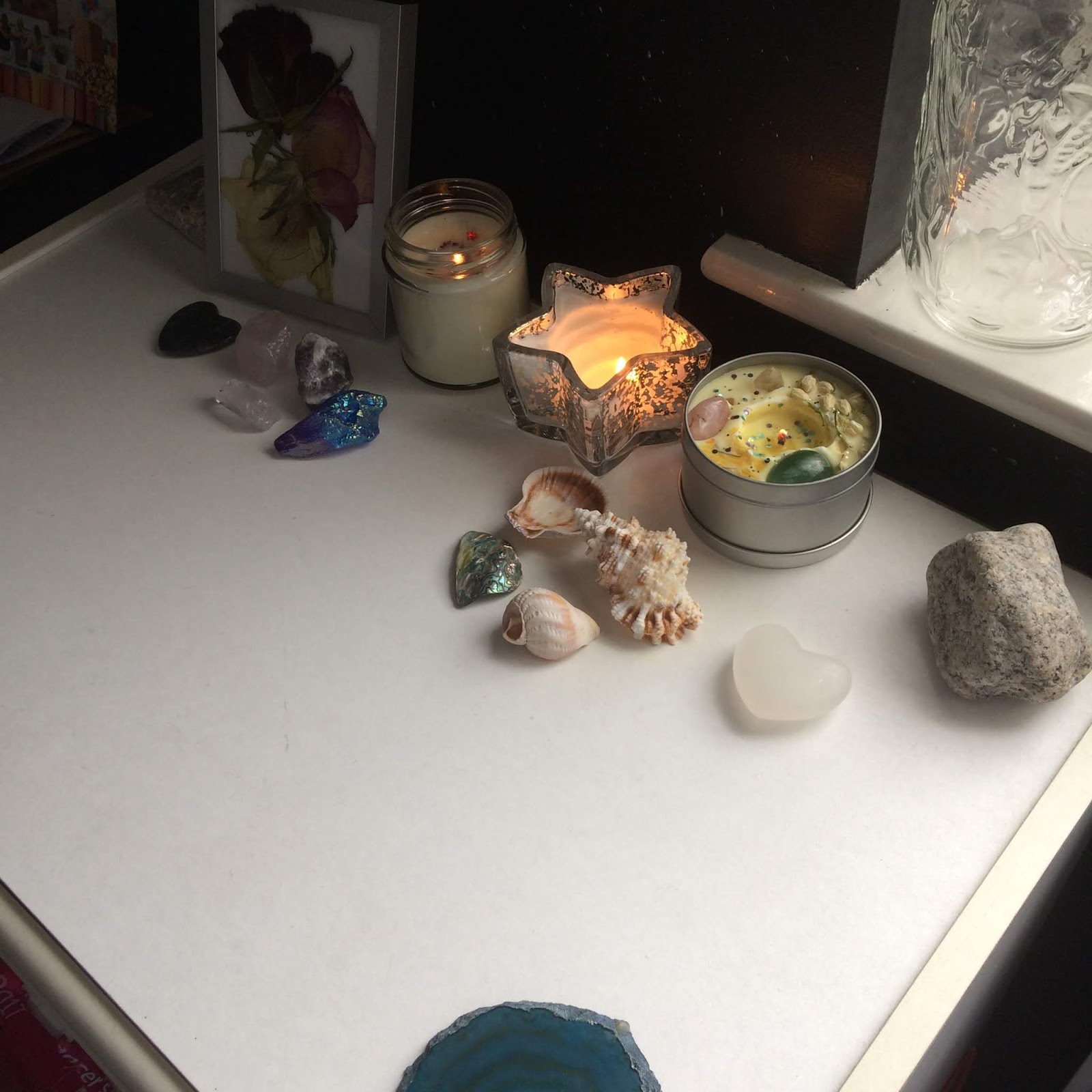 A photo, taken from a diagonal position, of my everyday altar, with my three lit container candles, including the Ostara candle, a small collection of crystals and shells, and a pressed roses in a frame
