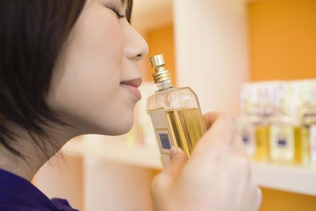 Mulher sentindo aroma de perfume