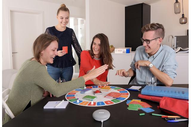Vier Menschen spielen ein Brettspiel an einem Tisch