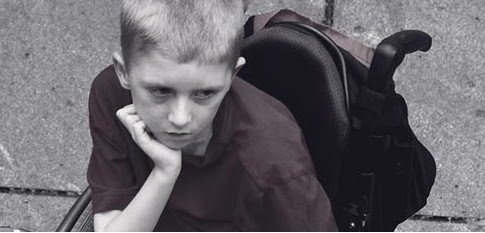 Boy in wheelchair watching something sad
