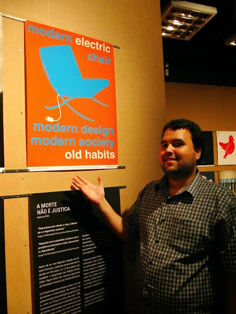 "Imagem onde aparece Rennan com um cartaz ao lado ""Modern electic chair.  Modern design modern society old habits"""