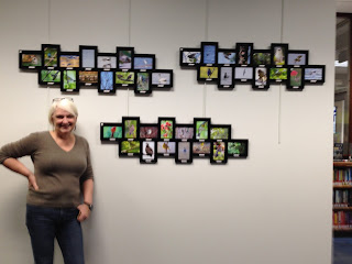 Photographer Vickie Bailey poses beside her photographs of local birds.