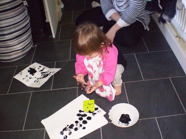 Eldest using blocks to print black paint on white paper