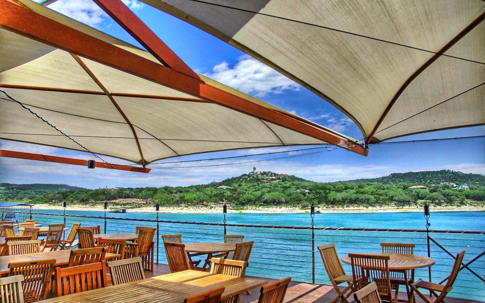 Parasollen en tafels aan het water