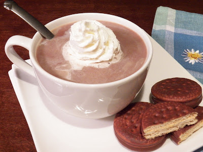 hot cocoa with sweetened condensed milk, dollop of whip cream, brown round cookies