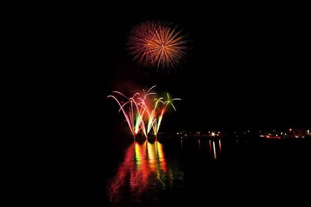 fireworks reflect over water