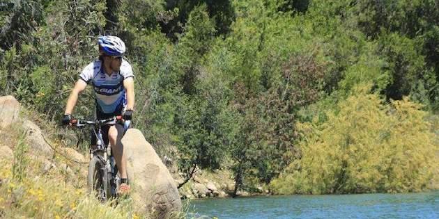 Ciclista al costado de un río