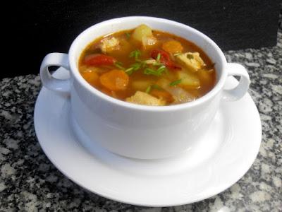 Sopa de col con trozos de pollo y hortalizas picadas