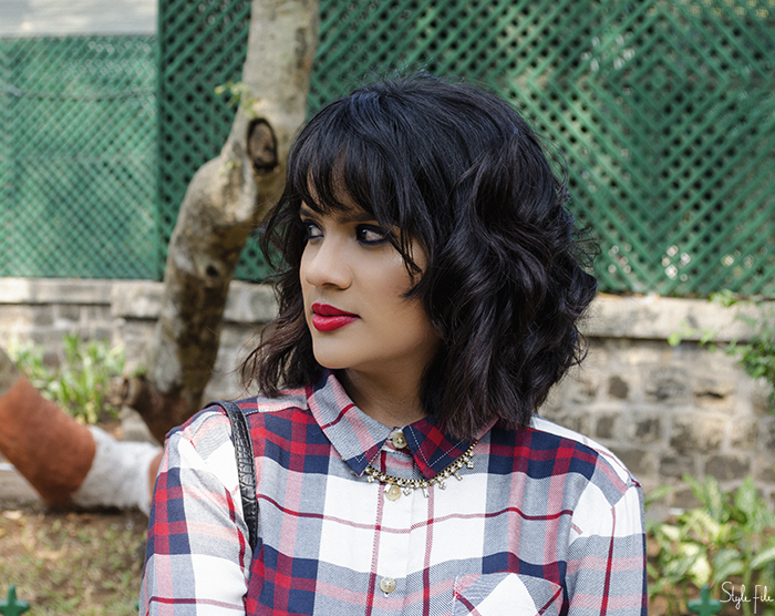 Image of Indian fashion blogger wearing a plaid checked shirt, tutu skirt, red high heels with a mini bag, collar necklace and highlighted skin