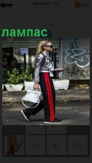 По улице идет девушка с сумочкой и на ней брюки одеты с лампасами красного цвета