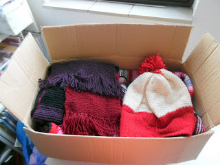 Donation box filled with crochet items like scarves, afghans and hats