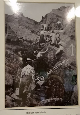 Old photo showing a group of men and women climbing up the last section of the M-M Trail