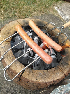 Hot Dogs being Roasted over an Eco Grill Open Fire