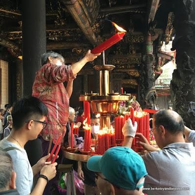 lighting candles at Longshan Temple/Mengjia Longshan Temple in Tapei, Taiwan