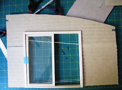 Wall of a dolls' house kit, with weatherboarding cut to size and a sliding door dry fitted.
