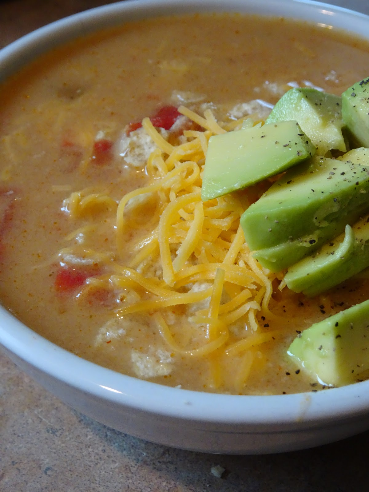 a bowl of warm soup with avocado