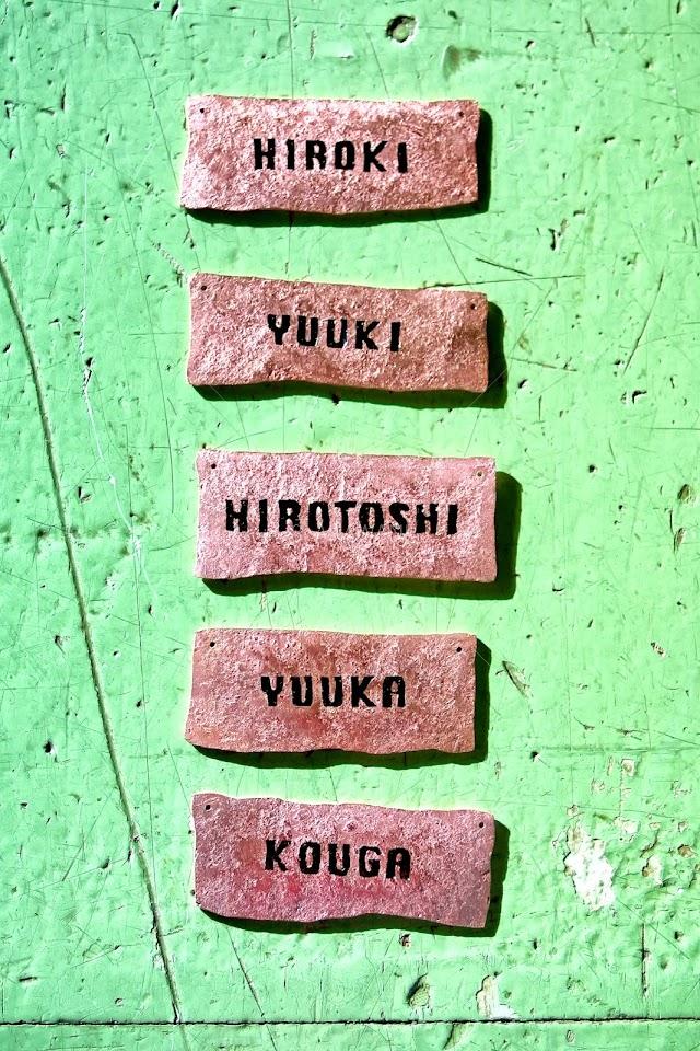 小さな銅板を鍛造したプレートになネームを彫り七宝を施したプレートが縦に五つ並ぶ