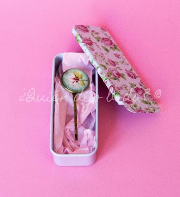Caja metálica con estampado de flores vintage y horquilla sobre papel de seda