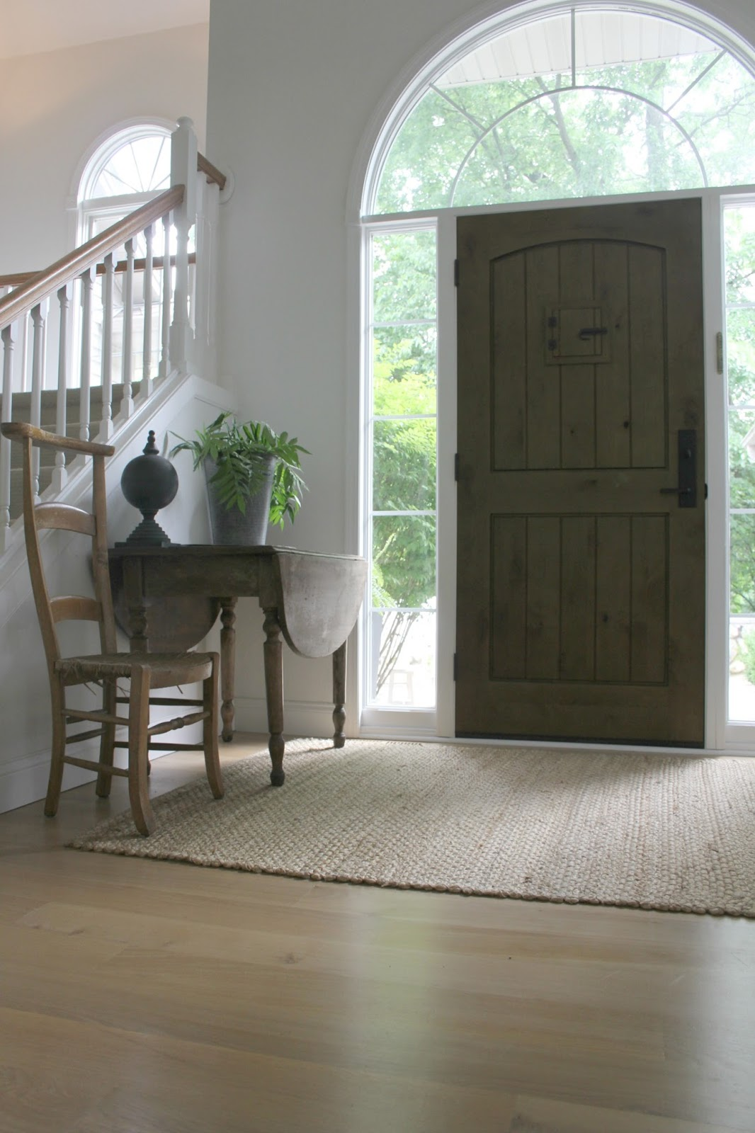 CKnotty rustic alder wood planked front door with speakeasy in a lofty entry with antique dropleaf table, dried hydrangea, and French prayer chair  within a European Country cottage by Hello Lovely Studio.