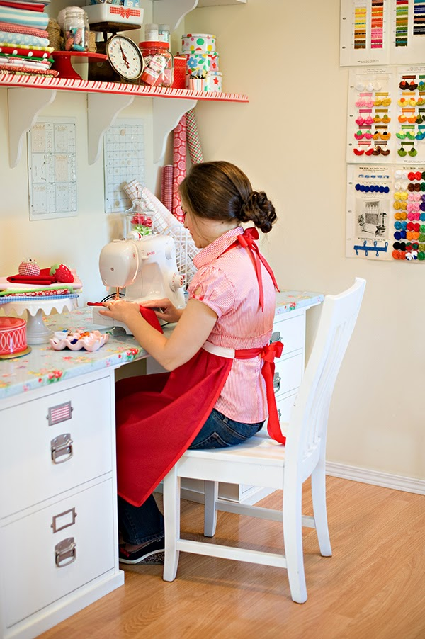 Retro crafting with the Farm Chicks - sewing room - At work! Look at those fabulous wedge shoes! I'm quite a big fan of the vintage catalogue cards on the wall with all the different colours.    I've also just spotted some more old school Cath Kidston patterns in the top corner, on the shelf there are some cake tins that are all stacked quite neatly!    It's quite clear that CK had a big part to play in this craft room, she has had a big part to play in the inspiration for my own craft room but I've gone for the light pastels instead of reds and bold patterns.