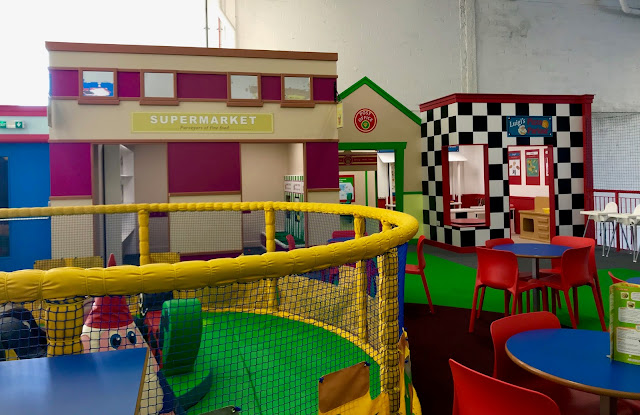A view of the end of toddler soft play across to a pretend pizzeria, supermarket and post office