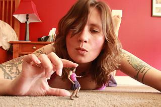 Mujer de tamaño normal, coge con los dedos a mujer diminuta