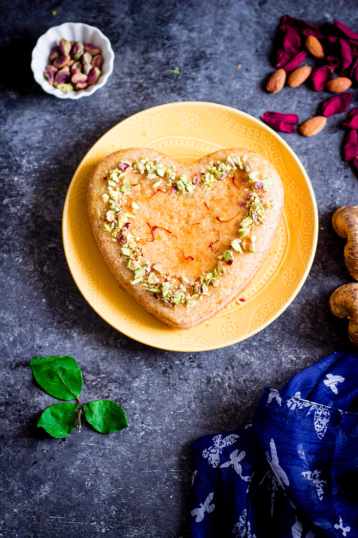 Persian love cake is an eggless rose and cardamom flavored cake made with almond flour and semolina. Brushed with an orange syrup and topped with chopped nuts.