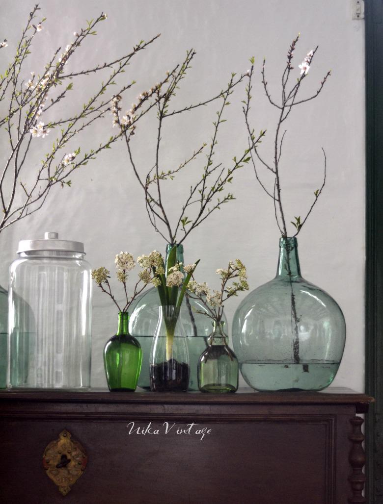 Una composición de cristal realizada con botes y damajuanas de gran tamaño, comienza la primavera en el recibidor de mi casa