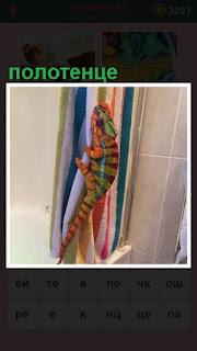 в ванной комнате ящерица ползет по полотенцу на верх