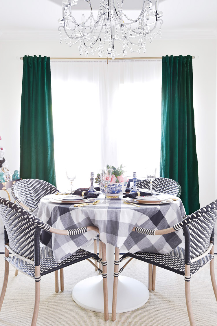 A small dining room space with a round white table, bistro chairs and emerald green velvet drapes. | #diningroom #diningspace #smallspace