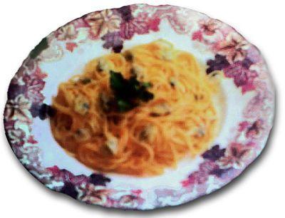 Plato de espaguetis o tallarines, con una hojita de albahaca.
