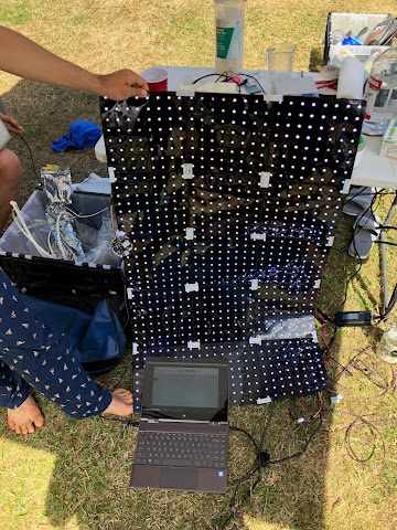 fifteen LED grids taped into a rectangle, held up by someone wearing pyjama pants, in front of a cluttered table, resting on grass