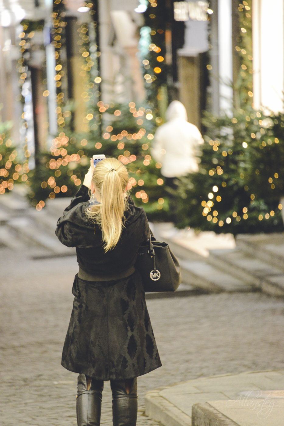 Beautiful blond Russian girl taking pictures on a Moscow street decorated for Christmas.