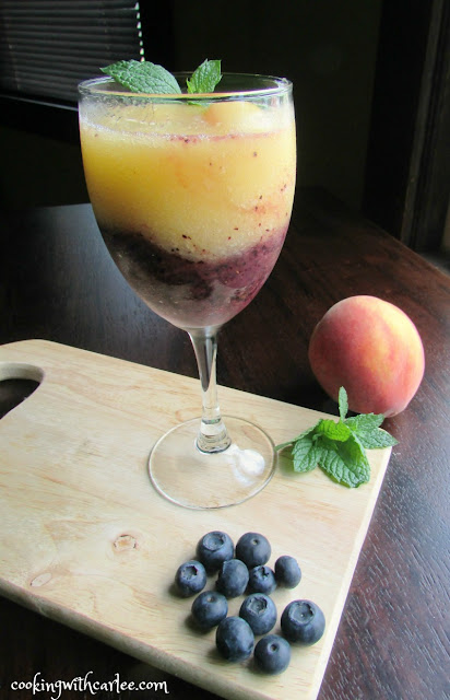 wine glass with a layer of peach wine slushy on top of blueberry wine slushy with a mint leaf garnish