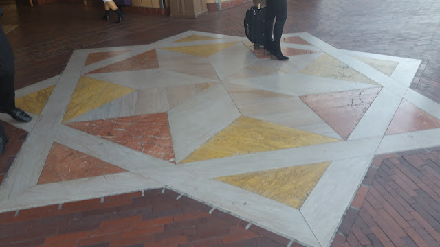 An eight sided star mosaic of brickwork on the ground.