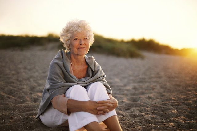 Older woman smiling on the beach at sunset