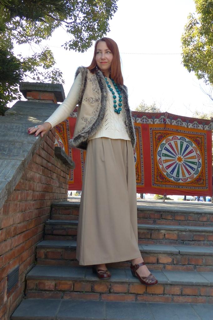 Fur trimmed vest over maxi skirt