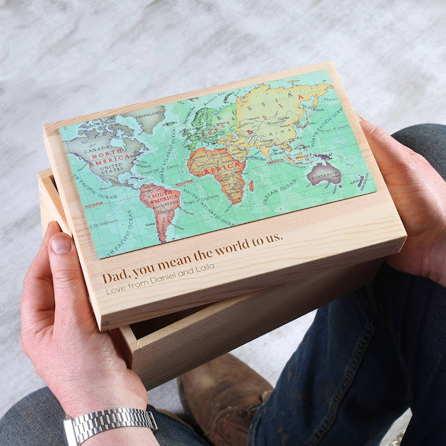 "A pair of hands holding a small rectangular wooden box with a map of the world on it and a message engraved saying ""Dad, you mean the world to us. Love from Daniel and Laila"""