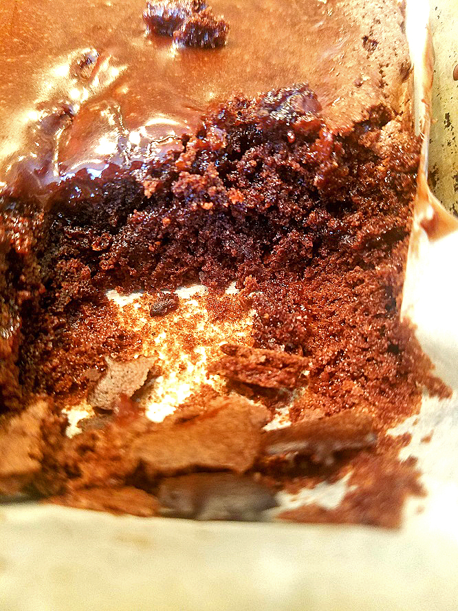 this is a baked cake with a piece missing to show how moist and decadent fudge it looks inside